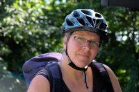 Foto von Alexandra mit Fahrradhelm auf dem Kopf und Rucksack auf dem Rücken.