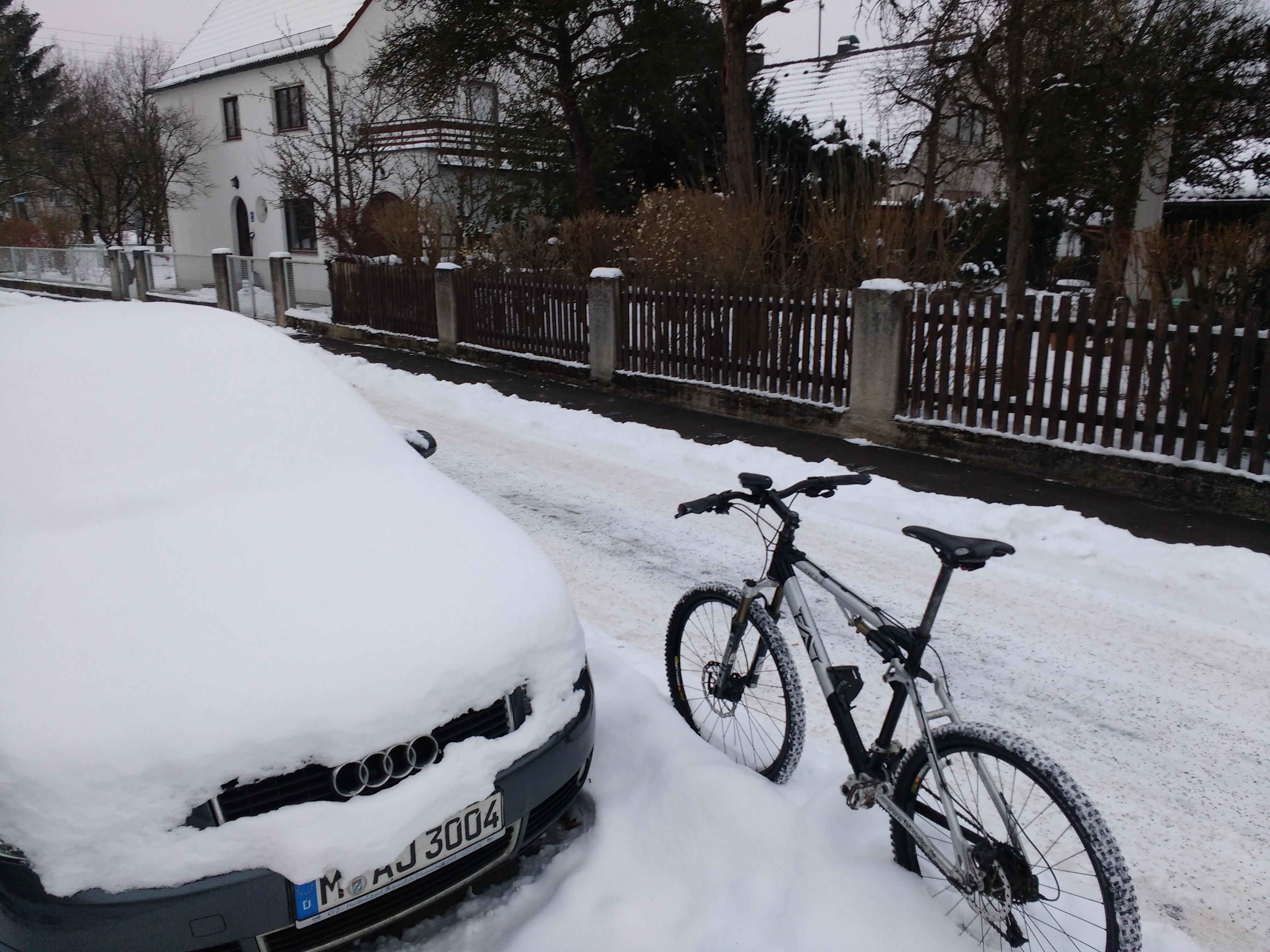 Fahrrad vor einem eingeschneitem Auto