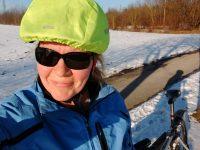Selfie einer Frau mit Sonnenbrille und Radhelm vor einem Schneefeld, in der Sonne