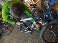 Mann schraubt an einem Mountainbike herum