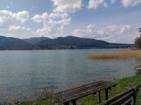 Blick über den See, Berge am anderen Ufer, Holzbank und Tisch im Vordergrund