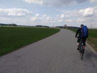 Weite Landschaft mit einem Radfahrer vor mir. Windig