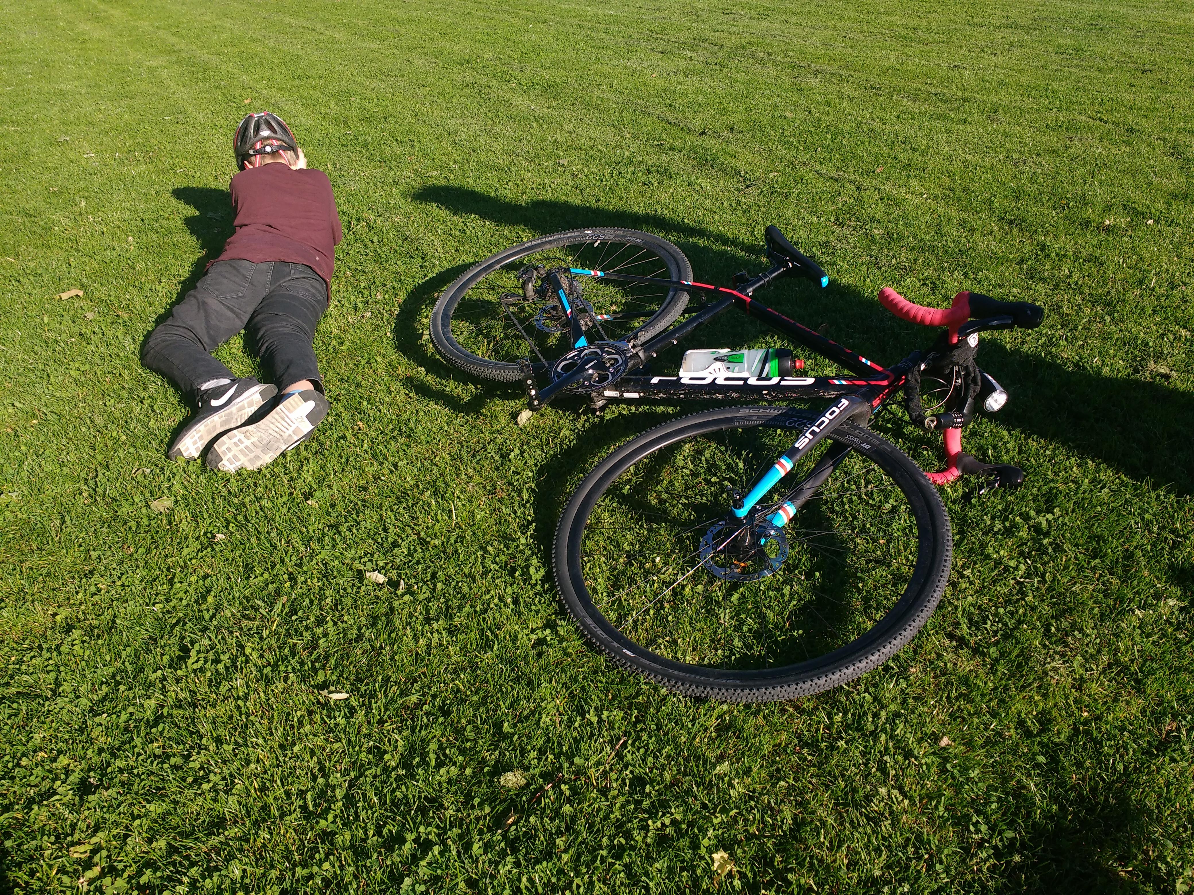 Junge und sein Fahrrad liegen auf einer Wiese in der Sonne.