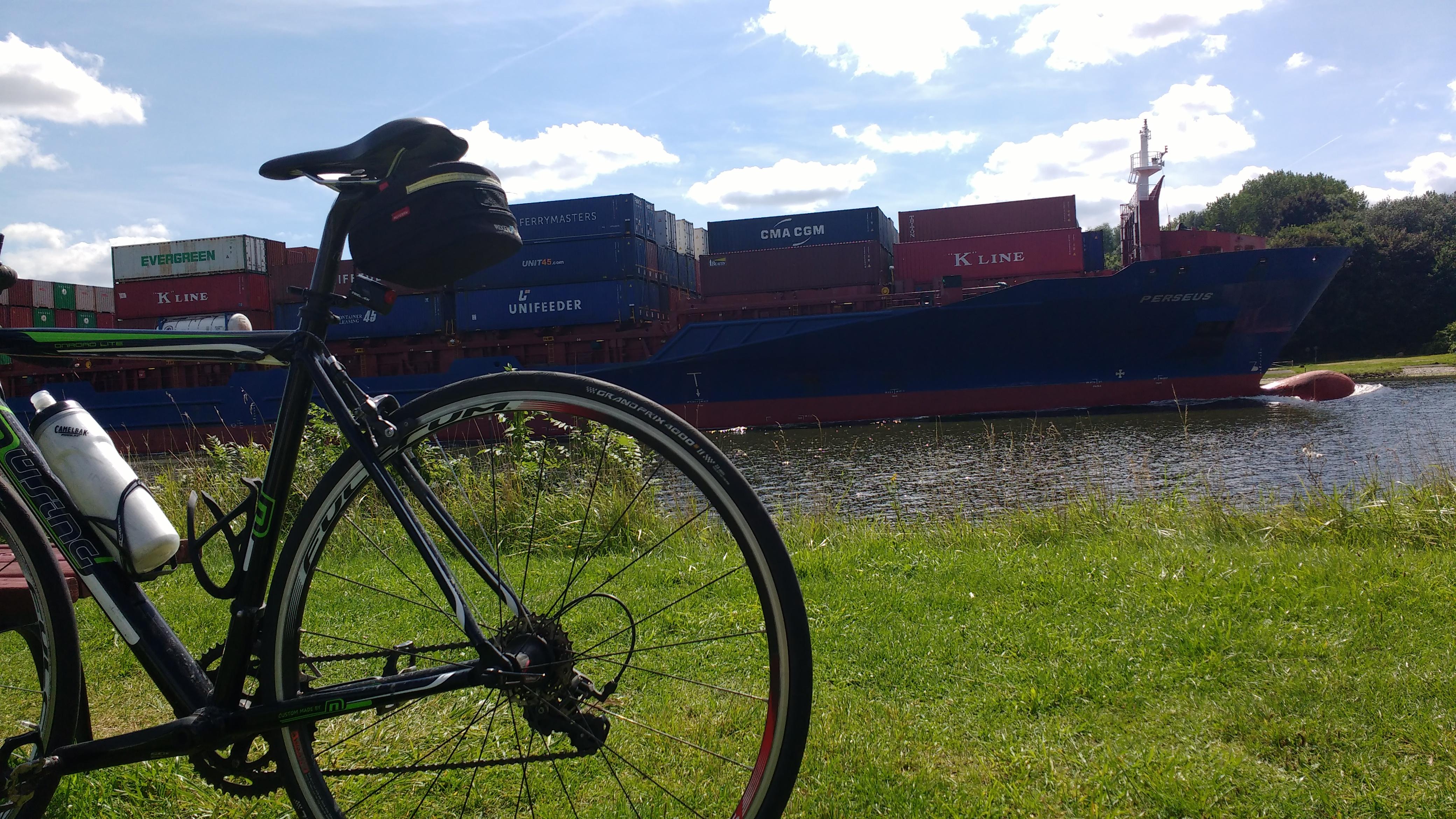 Mein Rad vor dem Nord-Ostsee-Kanal, und ein großer Frachter dahinter