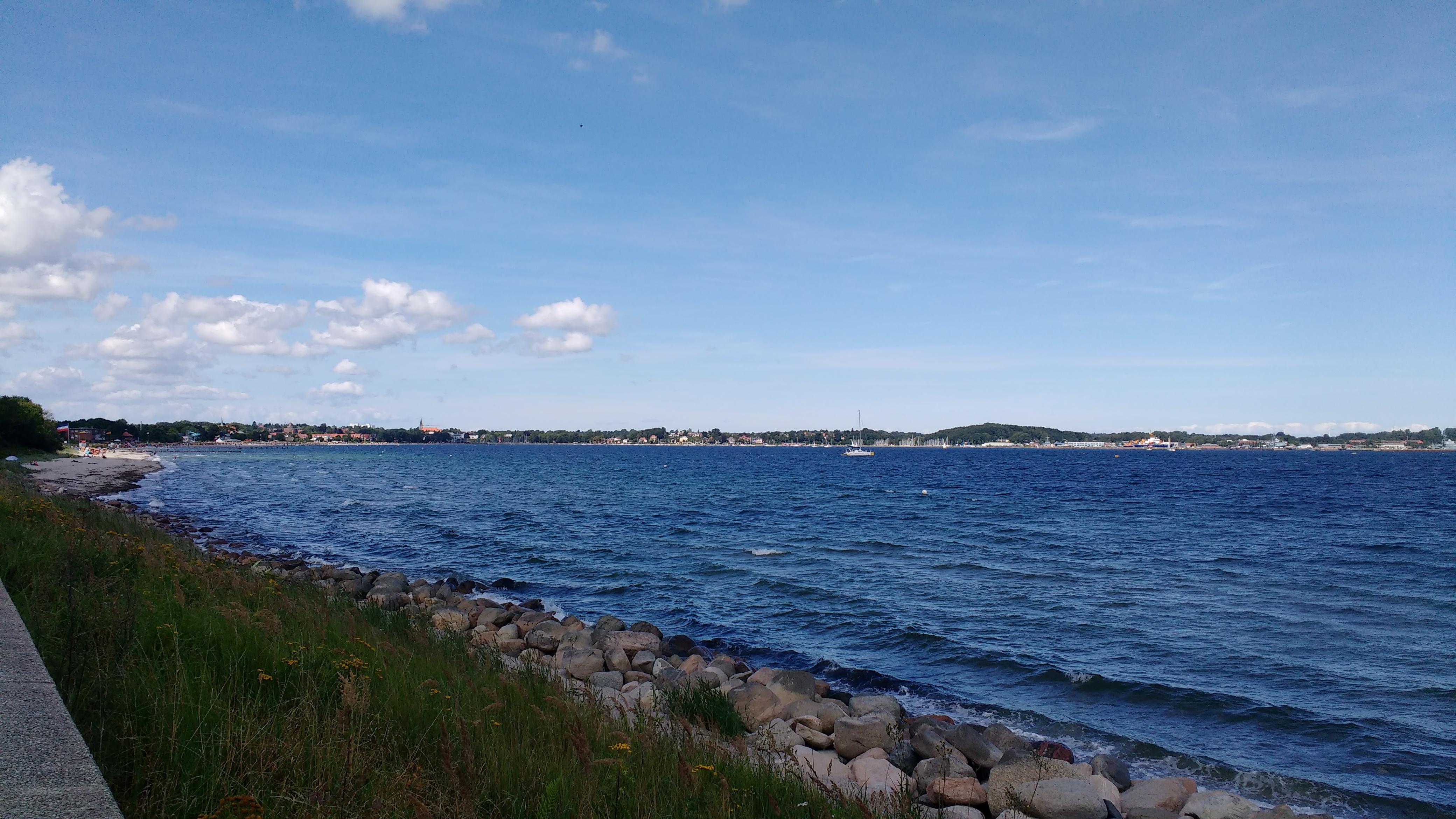 Meer, Strand, im Hintergrund eine Stadt