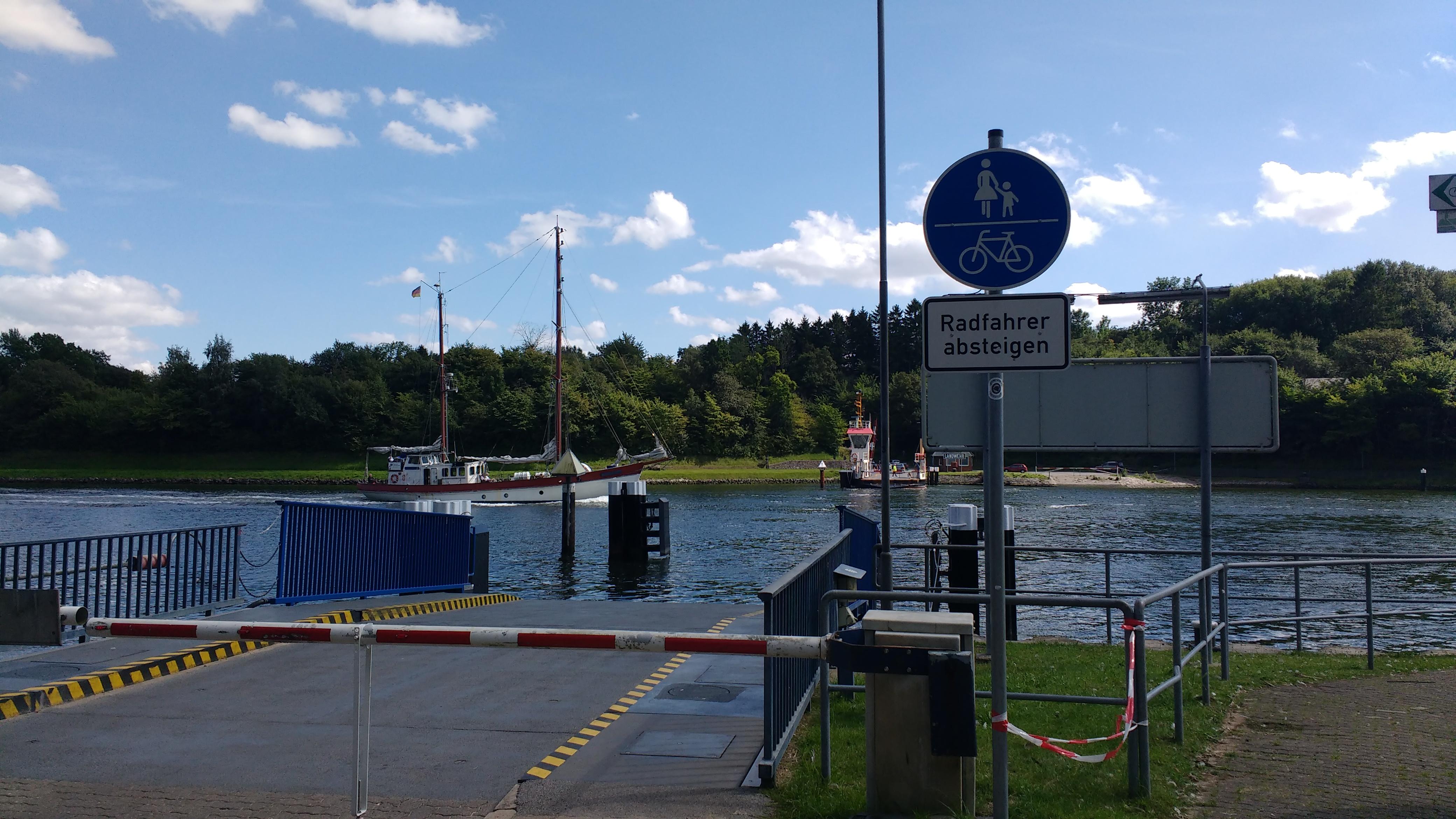 Fähranlegestelle, die Fähre ist am anderen Ufer, ein Segelboot Zweimaster im Mittelgrund