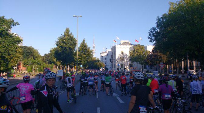 In der Morgensonne warten Frauen auf Rennrädern auf den Start