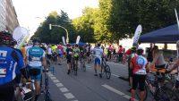 Rennradfahrer und -fahrerinnen, die ihr Rad durch die Finisher-Zone schieben.