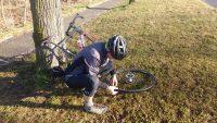 Mann in Rennradkleidung repariert einen platten Reifen.