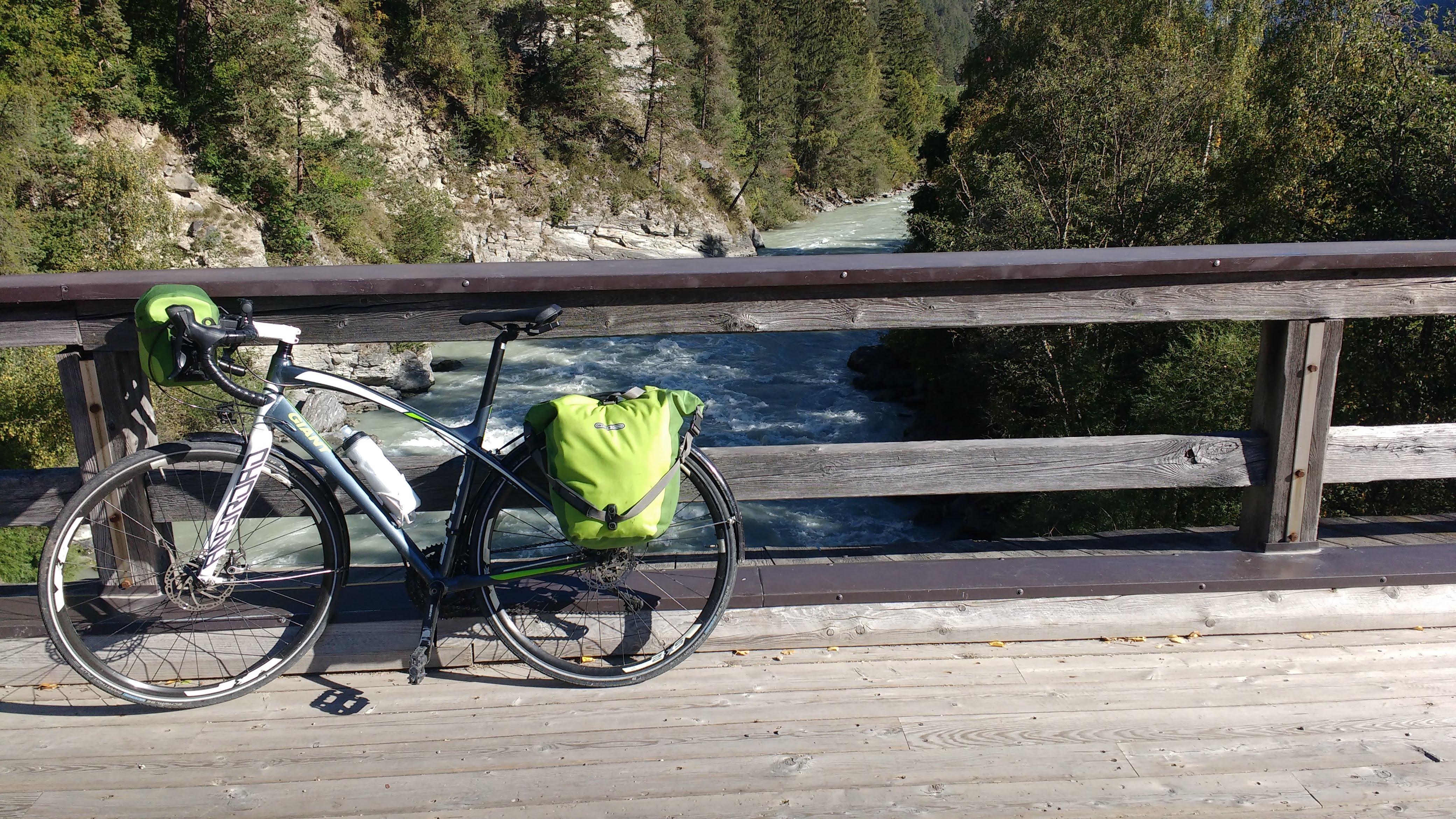 Fahrrad auf einer Holzbrücke über den Inn