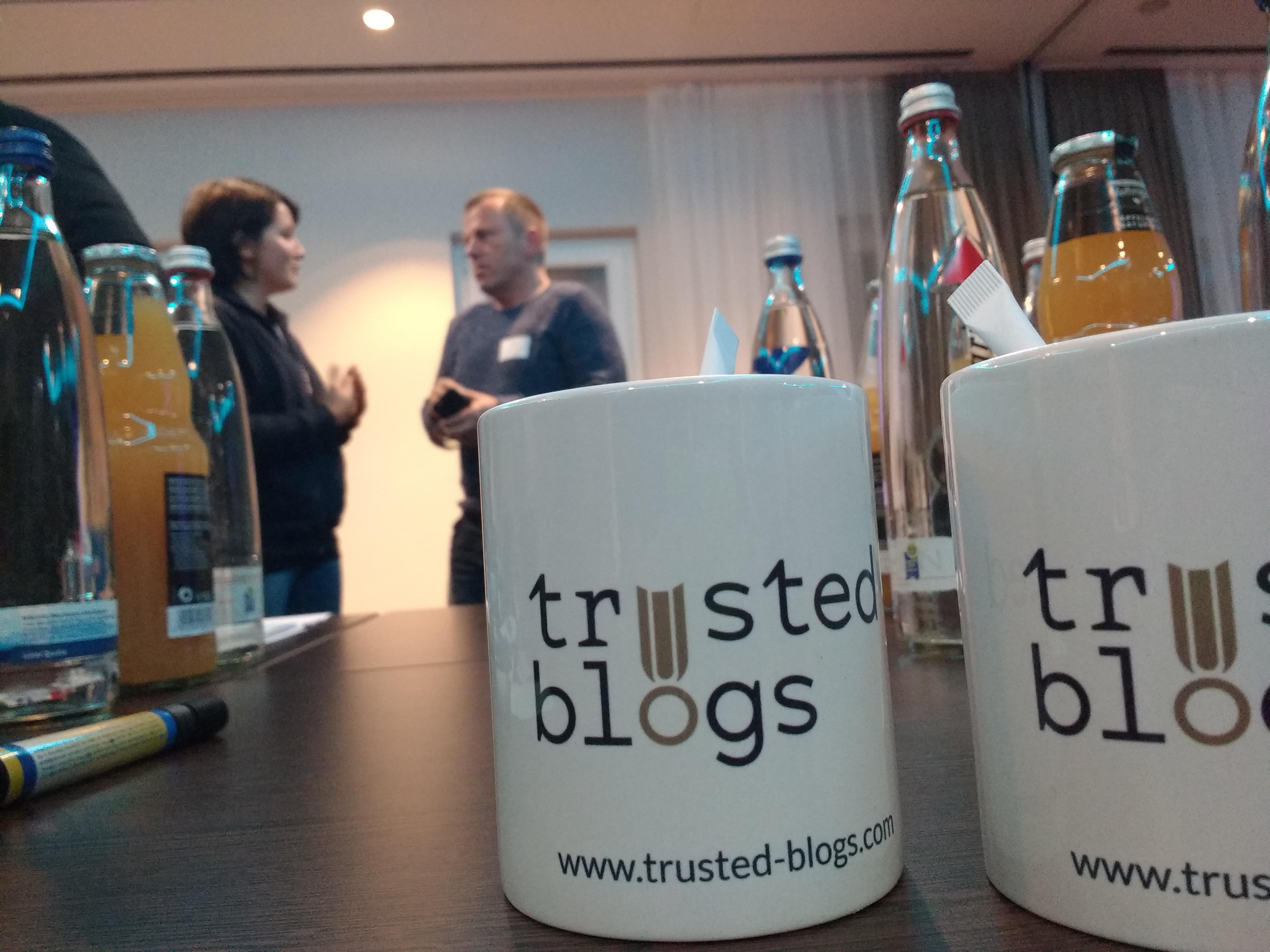 Zwei Tassen mit dem Logo der Firma Trusted Blogs, mit dem Geschäftsführer im Hintergrund