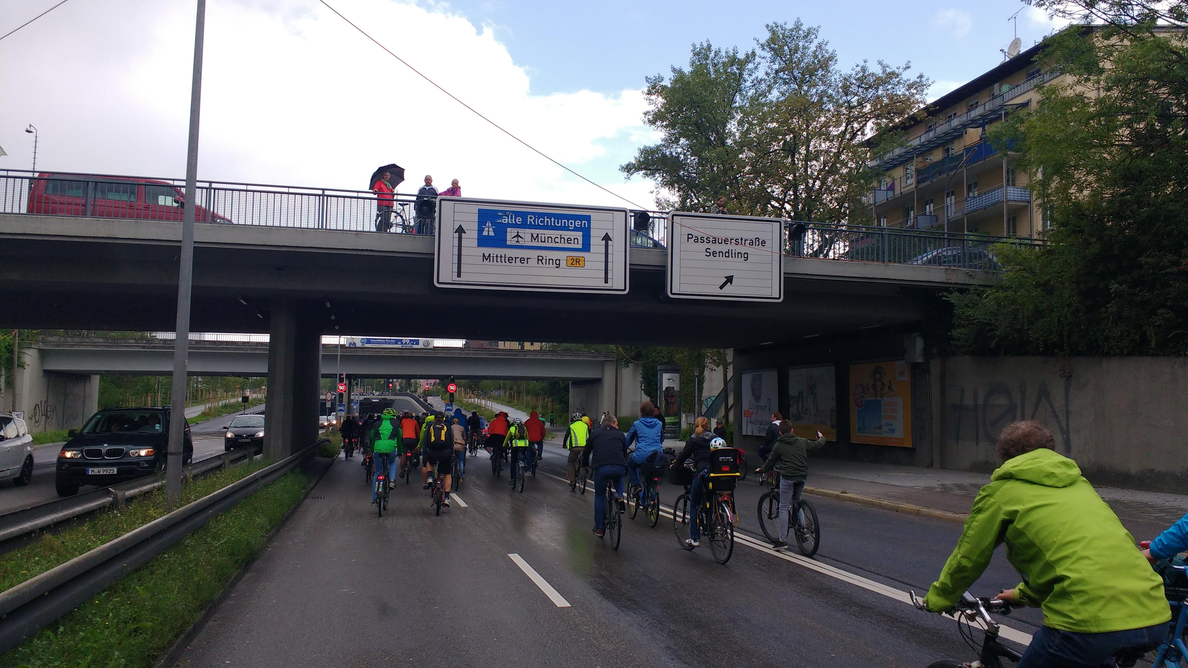 Radfahrer auf dem Mittleren Ring. Leute auf einer Brücke klatschen.